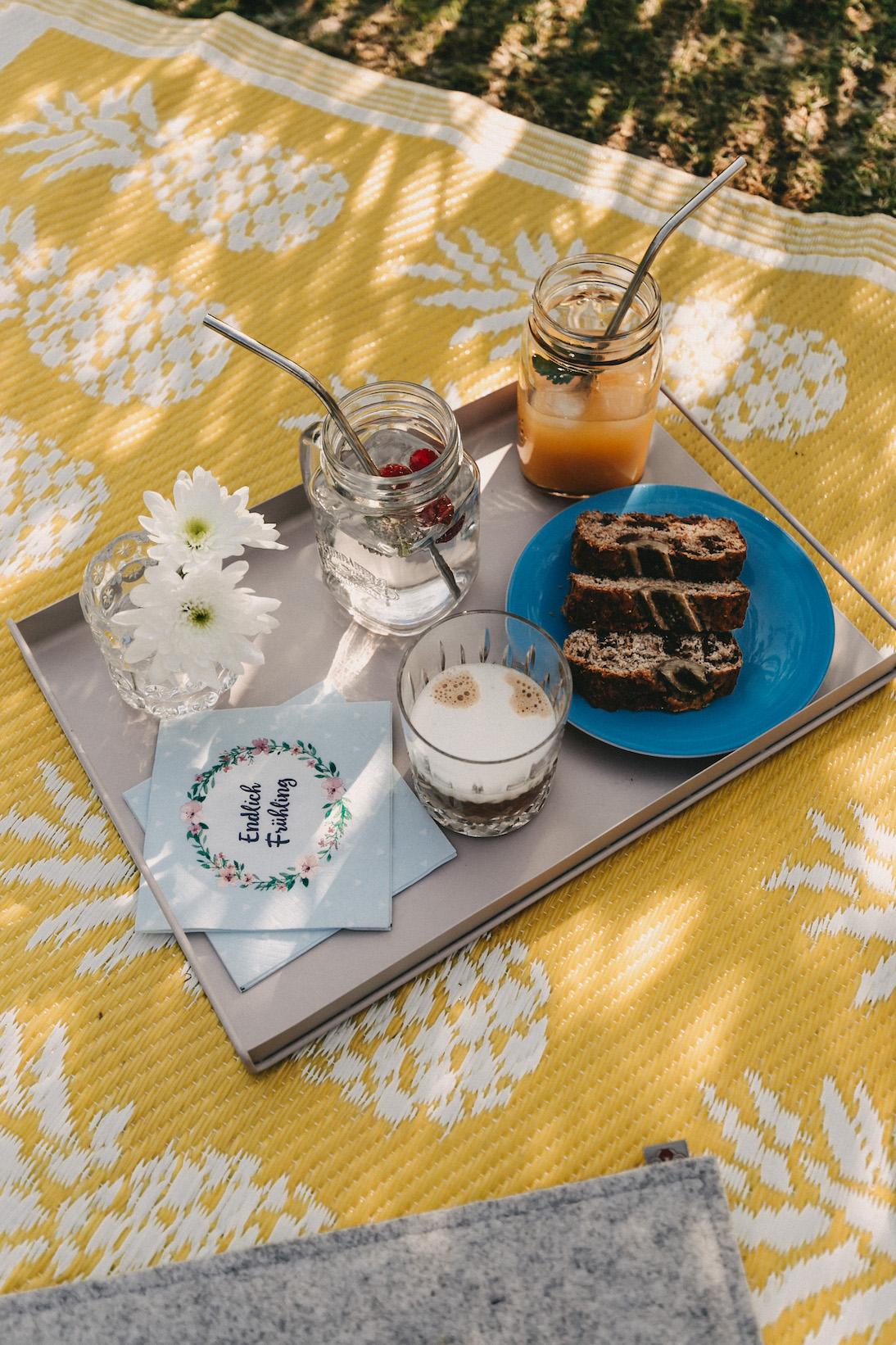Picknick mit Bananenbrot Kaffee und kalten Getränken auf gelber Outdoordecke