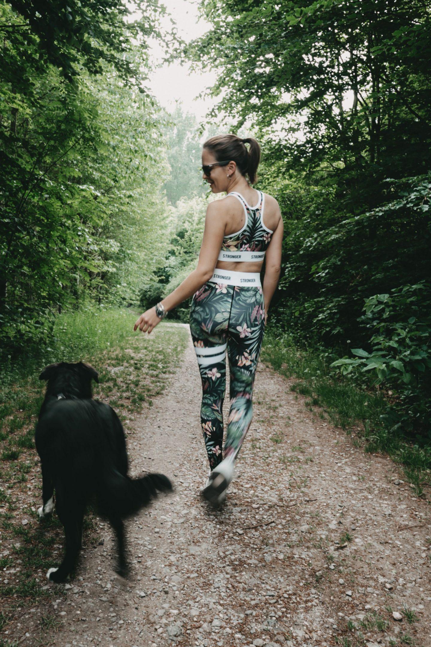 Frau im Wald mit Hund im stylischen Laufoutfit von Stronger